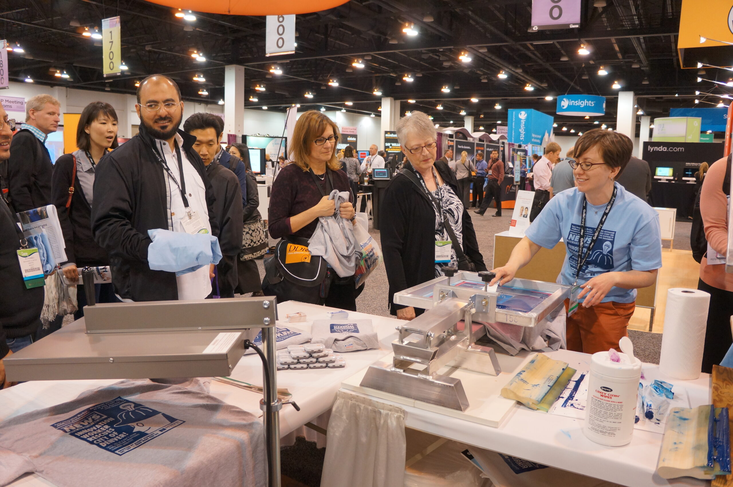 Booth-goers line up to screen print t-shirts at Intrepid Learning booth at ATD conference