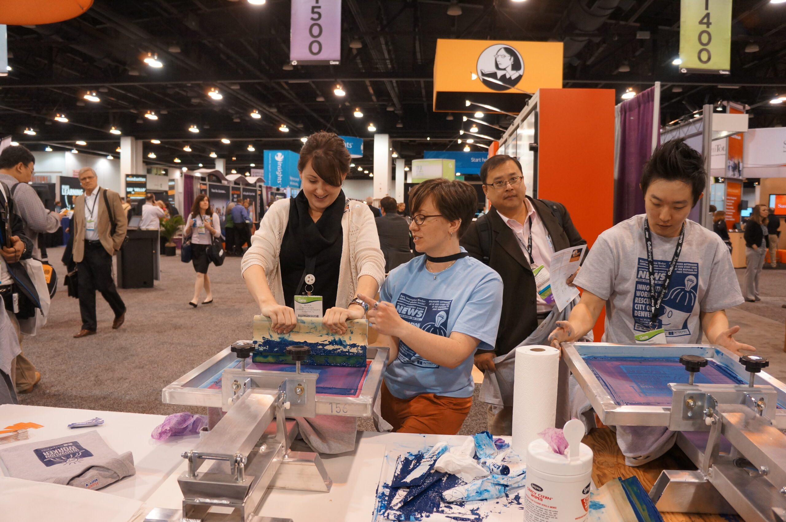 Booth-goer get assistance by Intrepid Learning team member while screen printing a t-shirt